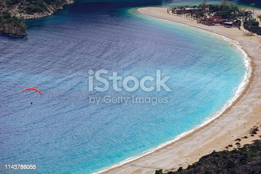 istock Paraglider tandem flying over the Oludeniz Beach and bay at idyllic atmosphere. Oludeniz, Fethiye, Turkey. Lycian way. Amazing Blue Lagoon detail. Summer and holiday concept. 1143786055