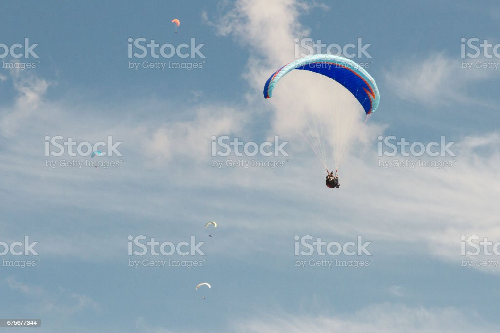 A para-glider up in the sky during a fly, with the campaign below him as background photo libre de droits