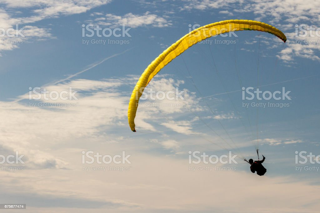 A para-glider up in the sky during a fly, with the campaign below him as background royalty-free stock photo