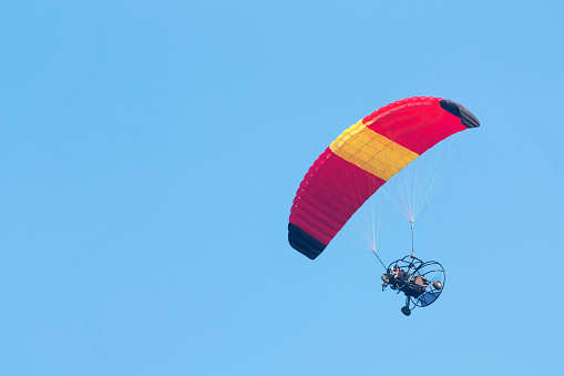 A paraglider with a motor on a sky background