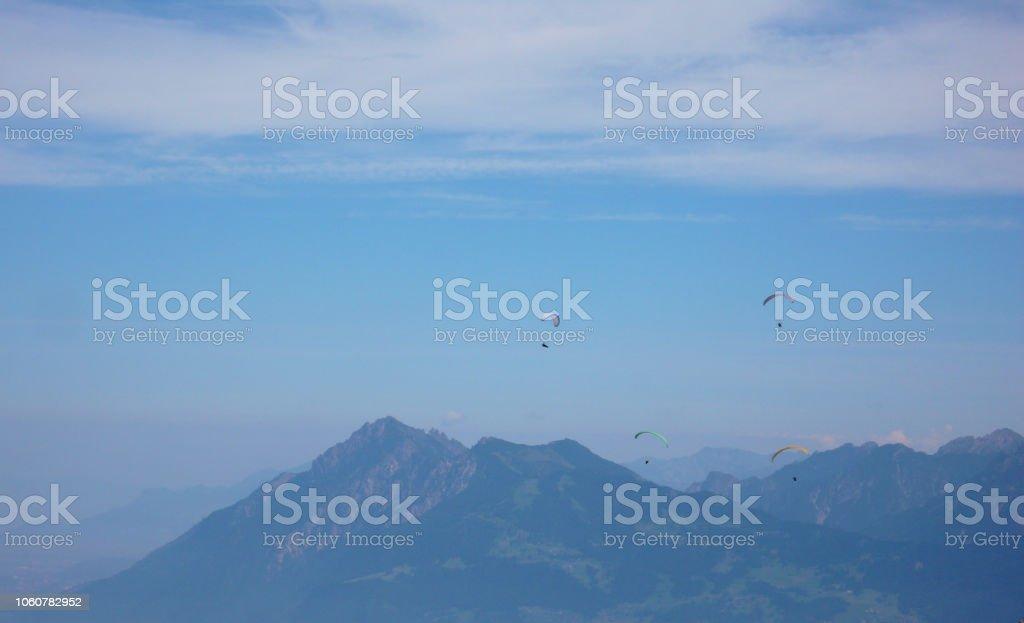 Gleitschirme fliegen in den Himmel über den Bergen der Schweiz – Foto