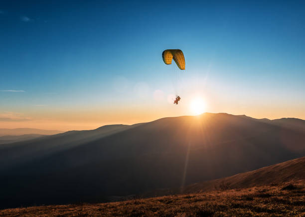 paragliders flying in the sky above the mountains stock photo