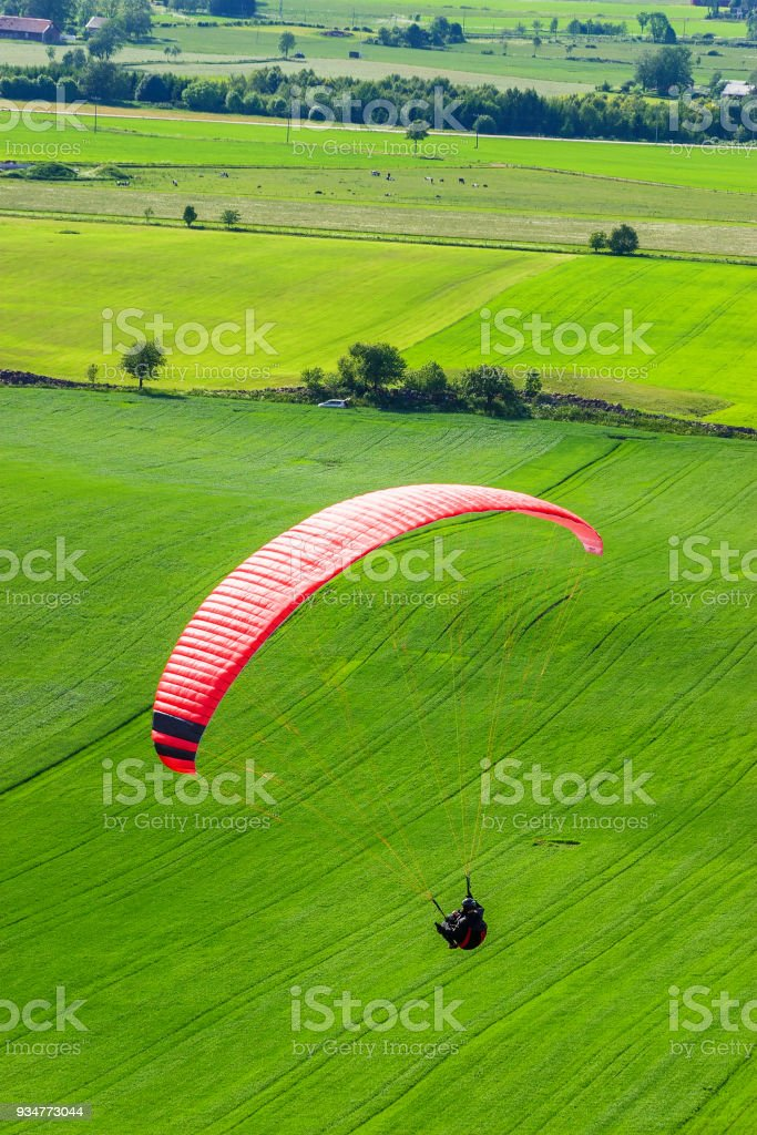 Paragliders over green fields in a rural landscape stock photo