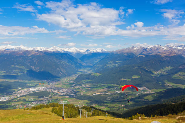 Paragliders take off near ski lift with Austrian Alps mountain range, view from Mount Kronplatz, South Tyrol, Italy Paragliders take off near ski lift with Austrian Alps mountain range, valley, snowy glacier mountains in background, Autumn view from Mount Kronplatz, South Tyrol, Italy, Europe bruneck stock pictures, royalty-free photos & images