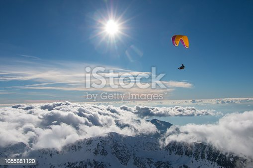 Paragliding above mountain peaks and clouds during winter sunny snowy day
