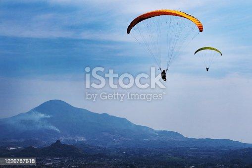 Paragliders flying over the city in Sumedang Regency, West Java, Indonesia.