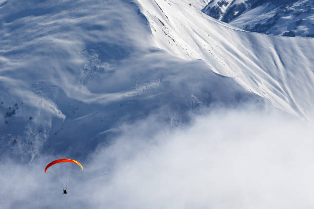 Paragliding at snowy mountains in haze - foto stock