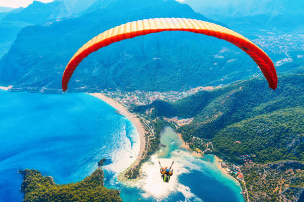 paragliding in the sky. paraglider tandem flying over the sea with blue water and mountains in bright sunny day. aerial view of paraglider and blue lagoon in oludeniz, turkey. extreme sport. landscape - parapente imagens e fotografias de stock