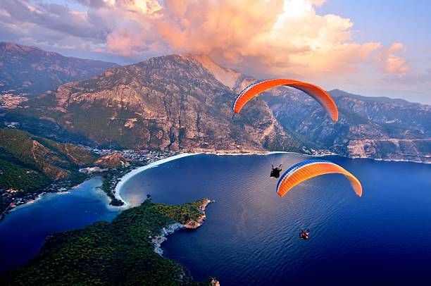 Paragliding into the sunset over the ocean Oludeniz beach, Fethiye, Turkey paragliding stock pictures, royalty-free photos & images