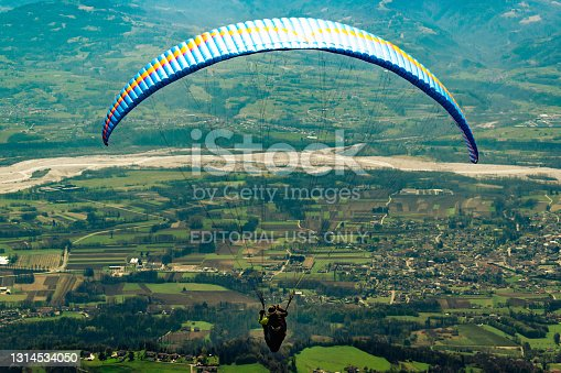 Panorama of the valley from the Ere Refuge. The first moments of the flight of a paraglider. San Gregorio nelle Alpi, Belluno, Italy