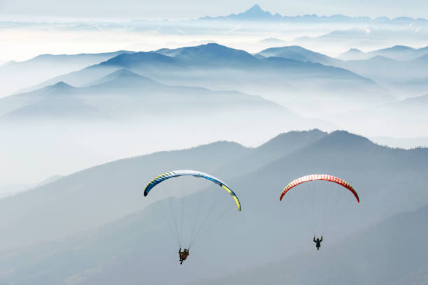 paragliding on the mountains couple flying over the mountains, italian Alps. Italy paragliding stock pictures, royalty-free photos & images