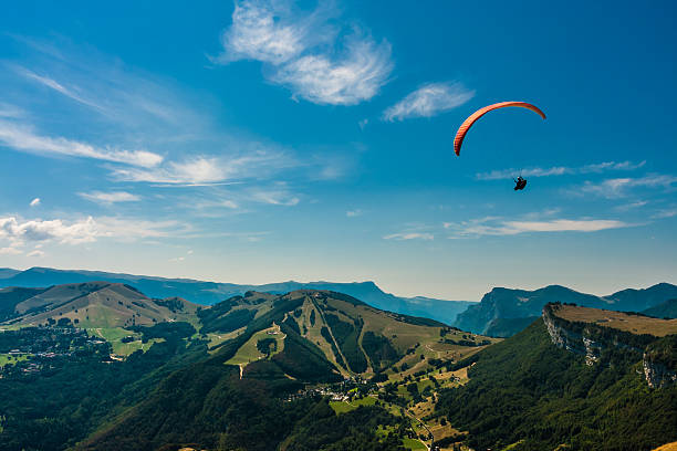 Paragliding on the sky Paraglider flies over the Dolomites to infinity paragliding stock pictures, royalty-free photos & images