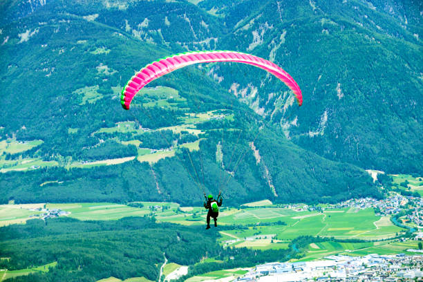 Paragliding over Mountains View of paraglider flying smoke jumper stock pictures, royalty-free photos & images