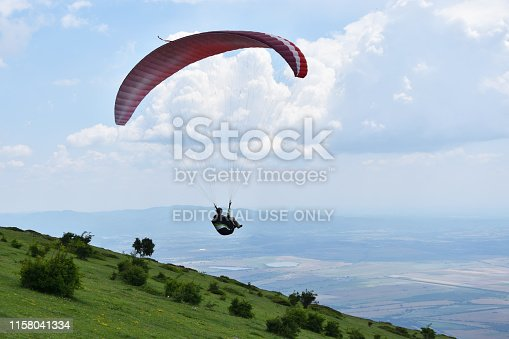 Sopot, Bulgaria - June 16, 2019: Silhouette of a young woman flying in the sky just launched her airfoil paraglider from the slopes of Stara Planina Mountain above the town of Sopot