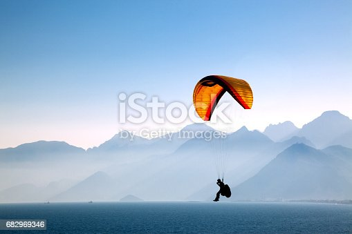 Silhouetted in the mountains with paragliding.