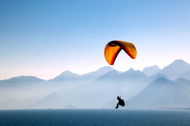 Paragliding Silhouetted in the mountains with paragliding. paragliding stock pictures, royalty-free photos & images