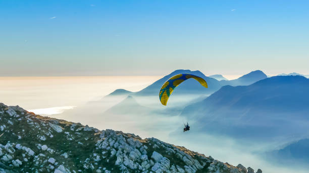 Paragliding tandem landing on the mountain slope Paragliding tandem flying over the mountains against lake during sunset. Freedom concept. Garda lake, Italian Alps paragliding stock pictures, royalty-free photos & images