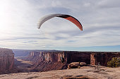 Young millennial male takeoff with para-glide from cliff in Utah in beautiful desert