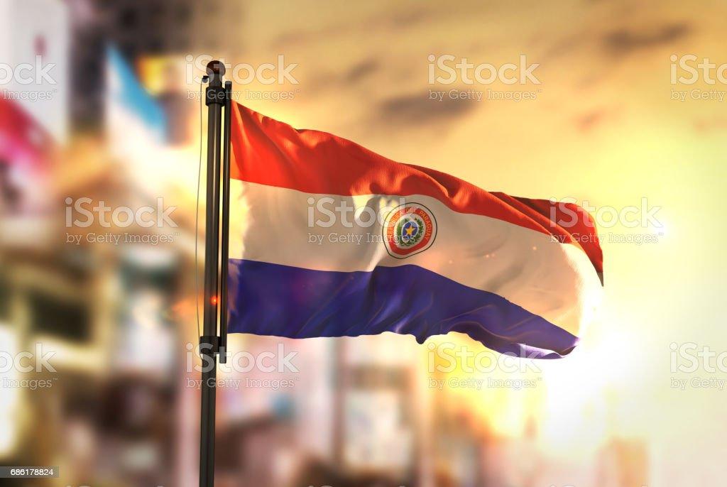 Bandera de Paraguay contra ciudad borrosa de fondo en contraluz amanecer - foto de stock