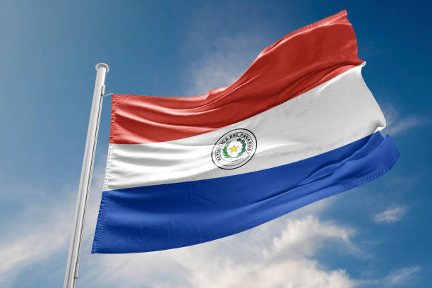 Paraguay Flag is Waving Against Blue Sky stock photo