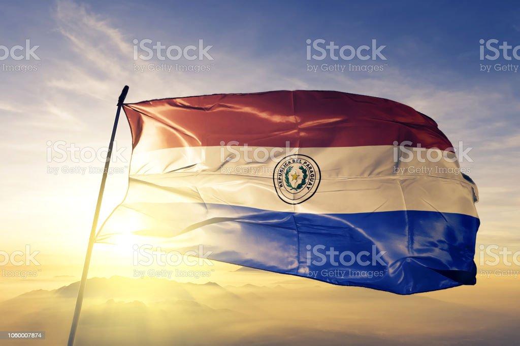 Paraguay bandera paraguaya paño tela ondeando en la niebla de la niebla de amanecer superior - foto de stock