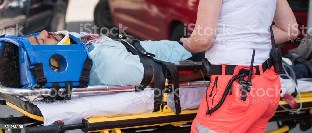 Paramedic helping injured man stock photo
