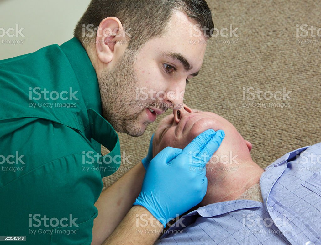 Paramedic nurse checks pulse of a patient who has collapsed stock photo