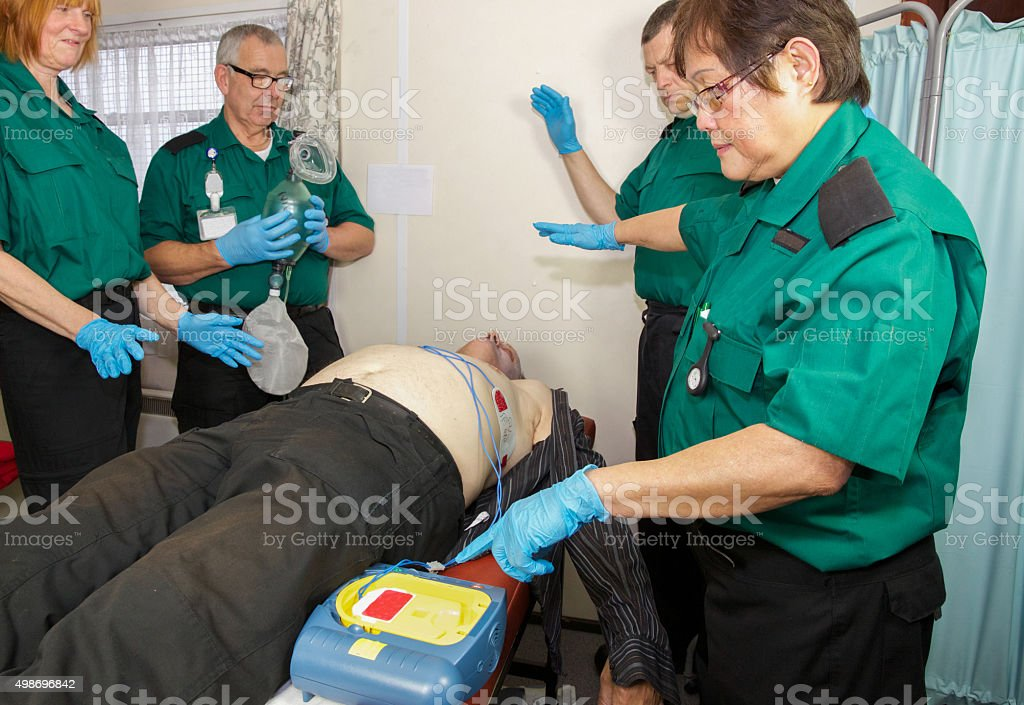 Paramedic nurses administer defibulator or defibrillator to revive a patient stock photo
