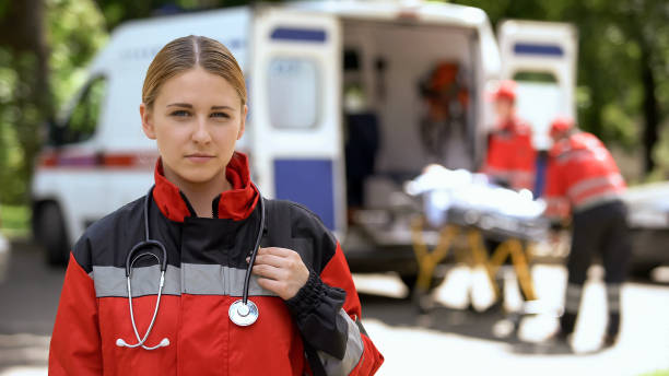 paramedic posing for camera, ambulance crew transporting patient on background - paramedic stock pictures, royalty-free photos & images