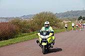"""Llanelli, Wales - April 10, 2011: Paramedic riding motorcycle at a public marathon run. Participants at the annual Human Being Active Welsh public marathon run on the Llanelli Millennium Coastal Path. This an amateur event open to the public"""