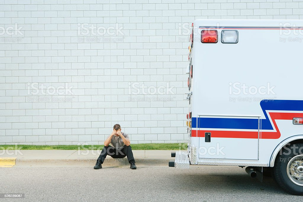 Paramedic sitting on pavement with head in hands stock photo