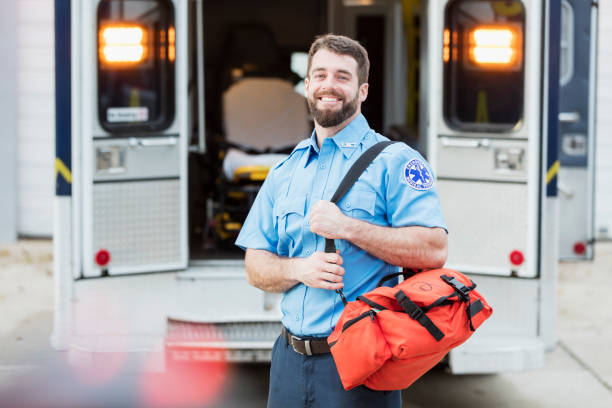 Paramedic standing at the rear doors of an ambulance stock photo