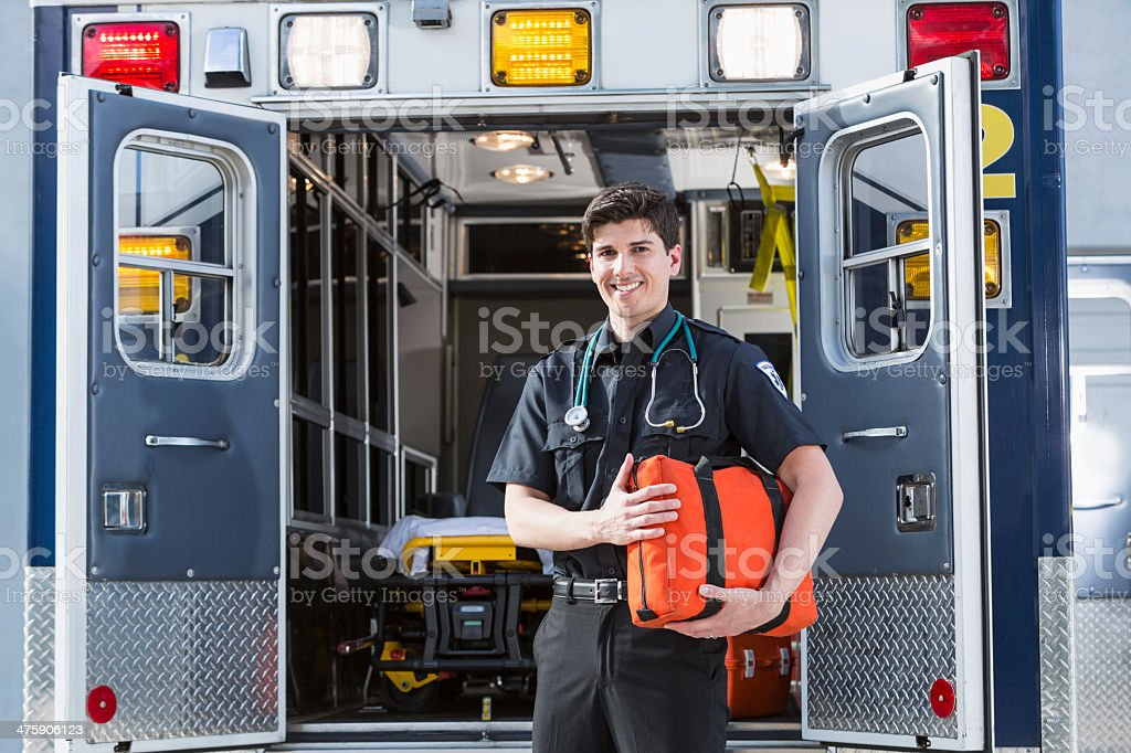 Paramedic standing by ambulance stock photo