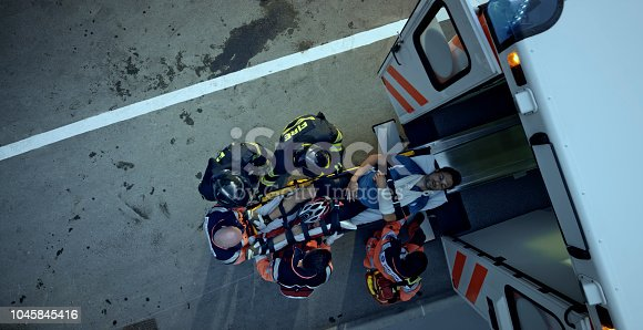 istock Paramedic team and firemen loading injured male cyclist on stretcher into ambulance 1045845416