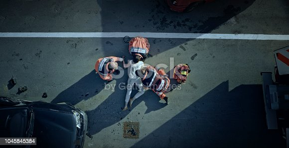 istock Paramedic team checking vital signs of car accident victim lying on ground at car crash site 1045845384