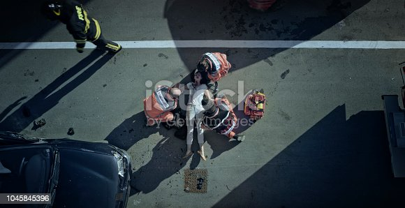 istock Paramedic team checking vital signs of car accident victim lying on ground at car crash site 1045845396