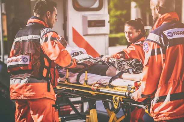 Paramedic team helping injured person stock photo