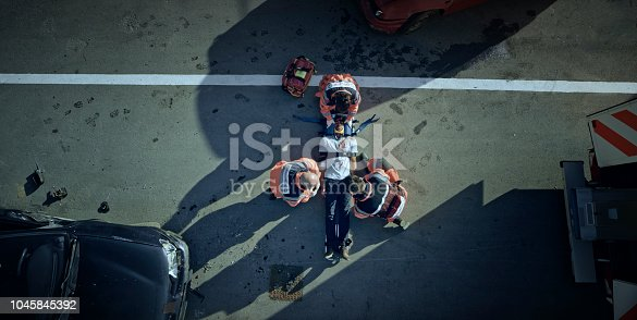 istock Paramedic team immobilizing male injured in car crash 1045845392