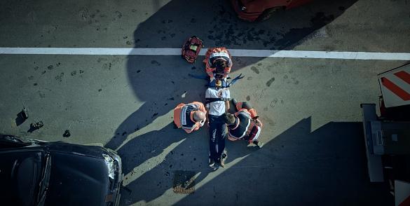 istock Paramedic team immobilizing male injured in car crash 1045845392