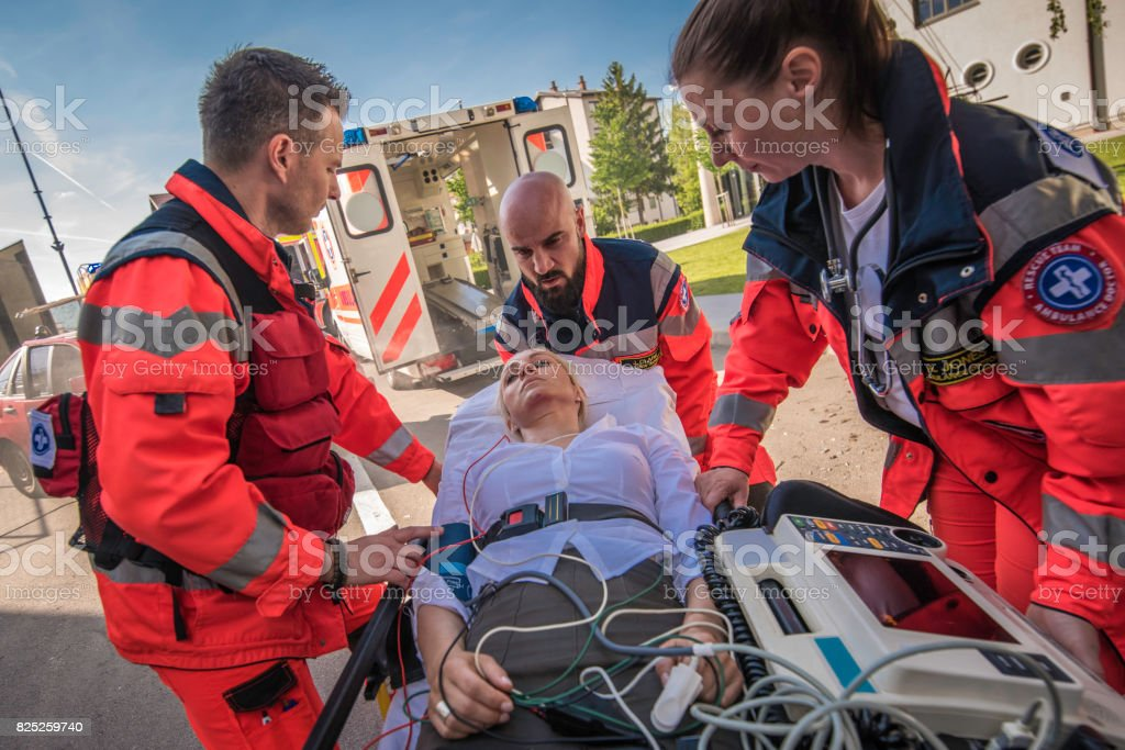 Female doctor and two technicians helping injured woman lying on...