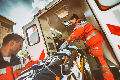 Paramedic team pushing stretcher with injured person towards ambulance.