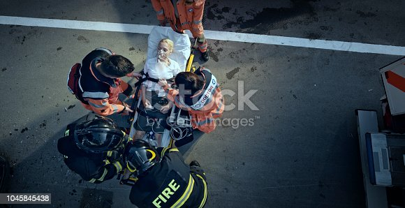 istock Paramedic team stabilizing injured woman on stretcher at scene of accident 1045845438