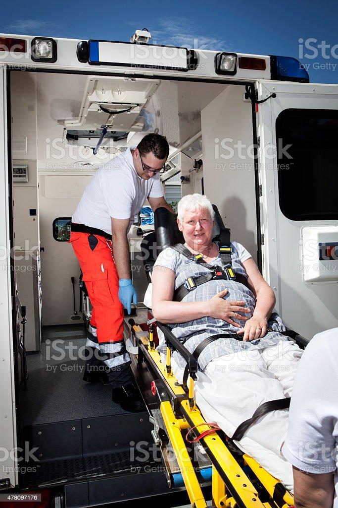 Medical emergency. Paramedics taking a senior woman on a stretcher...