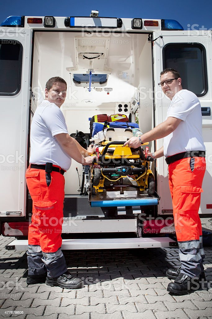 Two male paramedics standing behind an ambulance pulling out a...