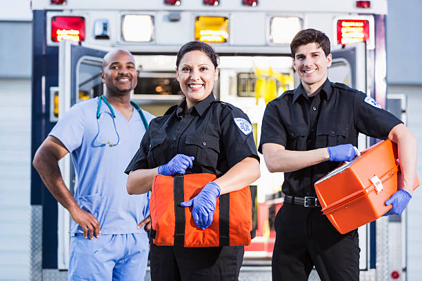 Paramedics and doctor outside ambulance Paramedics and doctor standing at rear of ambulance.  Focus on woman (30s, Hispanic). ambulance staff stock pictures, royalty-free photos & images