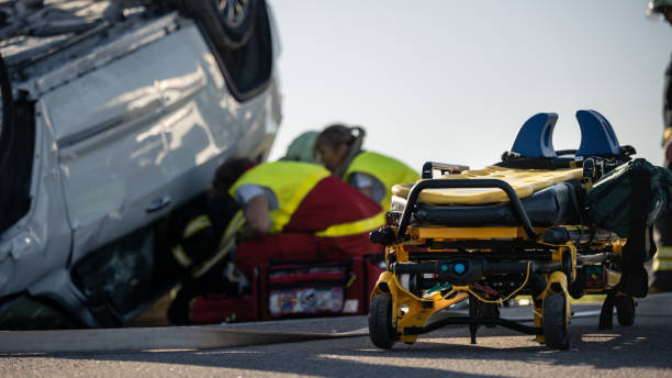 paramedics and firefighters arrive on the car crash traffic accident scene. professionals rescue injured victim trapped in rollover vehicle by extricating them, giving first aid and extinguishing fire - first responders zdjęcia i obrazy z banku zdjęć