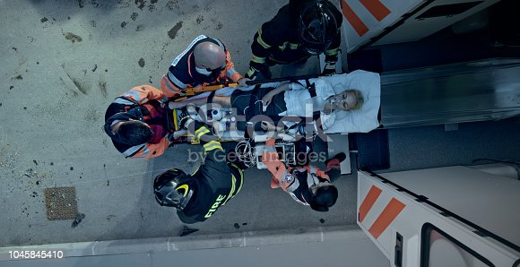 istock Paramedics and firemen loading female car accident victim on stretcher into ambulance 1045845410