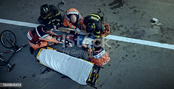 istock Paramedics and firemen raising an injured male cyclist onto stretcher at scene of accident 1045845424