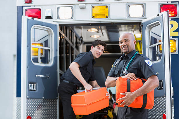 Paramedics at back of ambulance Multi-ethnic paramedics loading equipment into back of ambulance.  Focus on man on right (40s mixed race, Black and Hispanic). ambulance staff stock pictures, royalty-free photos & images