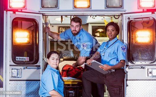 A multi-ethnic group of three paramedics at the rear of an ambulance, ready to climb in through the open doors.  The two women their male colleague have serious expressions.